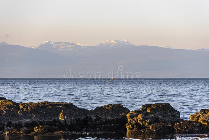 Rock formations near the body of water surrounded by mountains in the distance under a pink sky. A wide shot of rock formations near the body of water surrounded royalty free stock photography