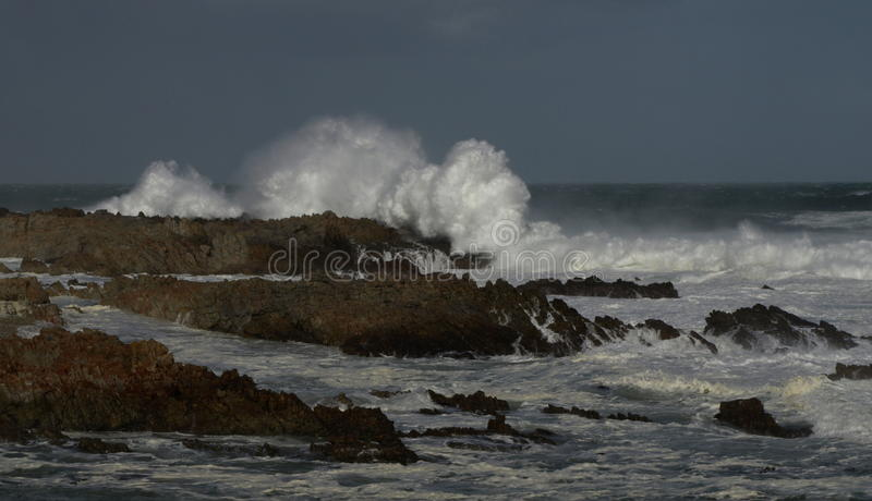 Rock formations in shallow waters. A view of rock formations covered with moss and waves hitting rocks causing water to splash stock photography