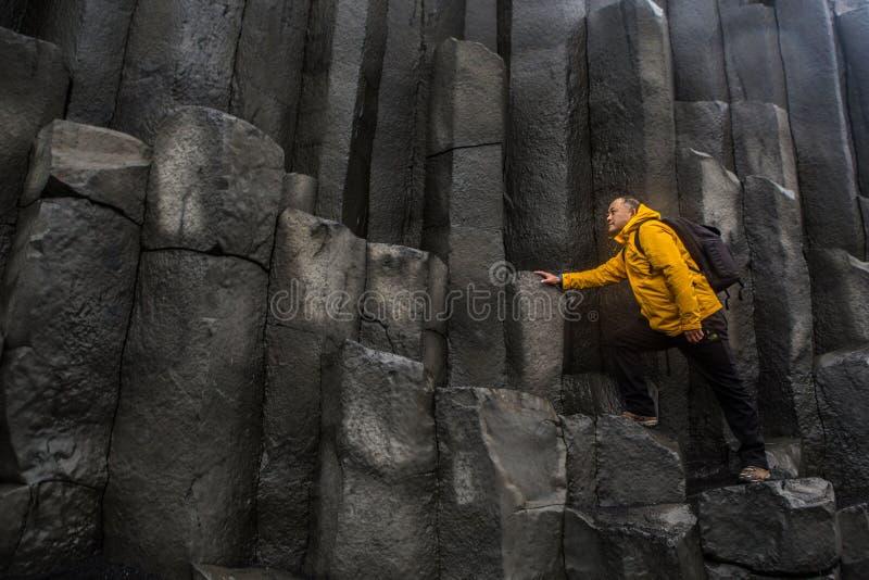 The rock foundation near black sand beach stock photography