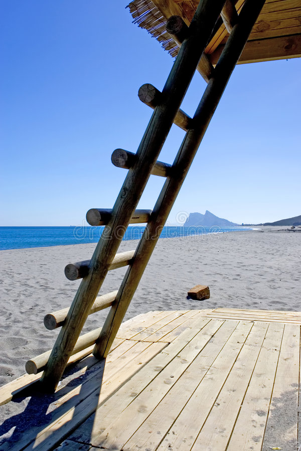 Rock of Gibraltar seen thourgh ladder on Spanish beach royalty free stock photos