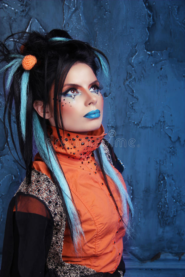 Rock girl with blue lips and punk hairstyle leaning against grunge wall stock image