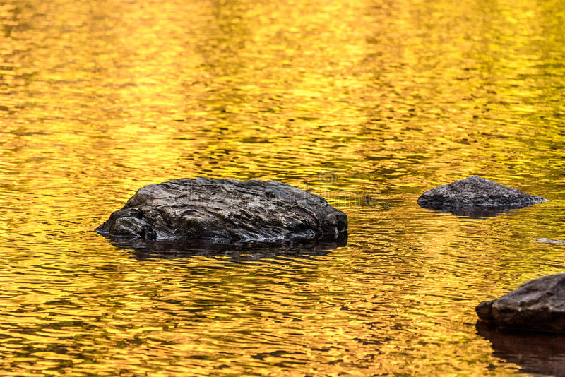 Rock and gold autumn lake reflections stock photography