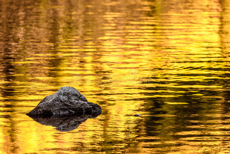 Rock and gold autumn lake reflections stock photo