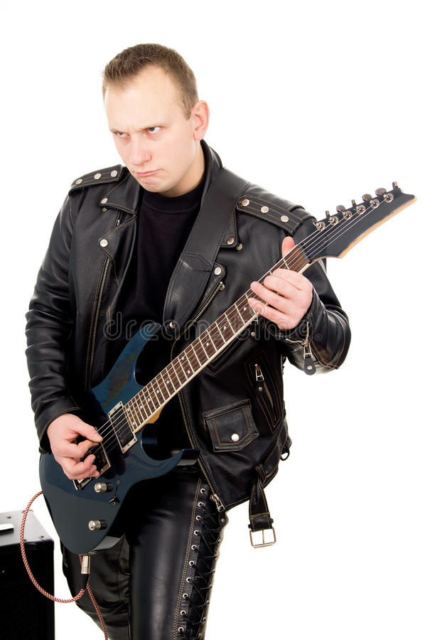 Rock guitarist in leather garments, with sound-amplifying equipment. Isolated on white background stock photo