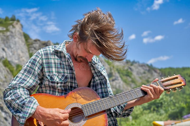 Rock guitarist playing a concert in nature on a sunny day royalty free stock images