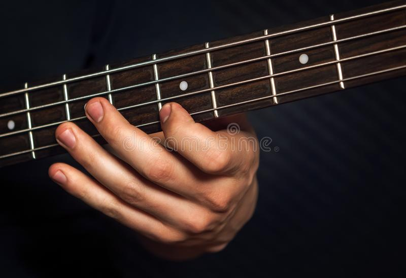 Rock guitarist practicing with bass guitar. royalty free stock photography