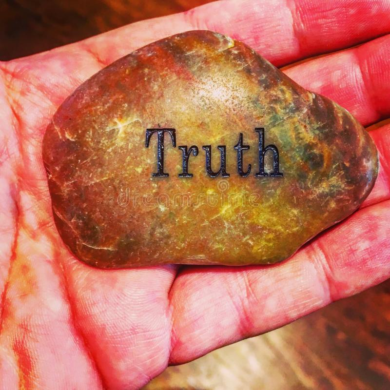 Rock in hand of truth stock photo