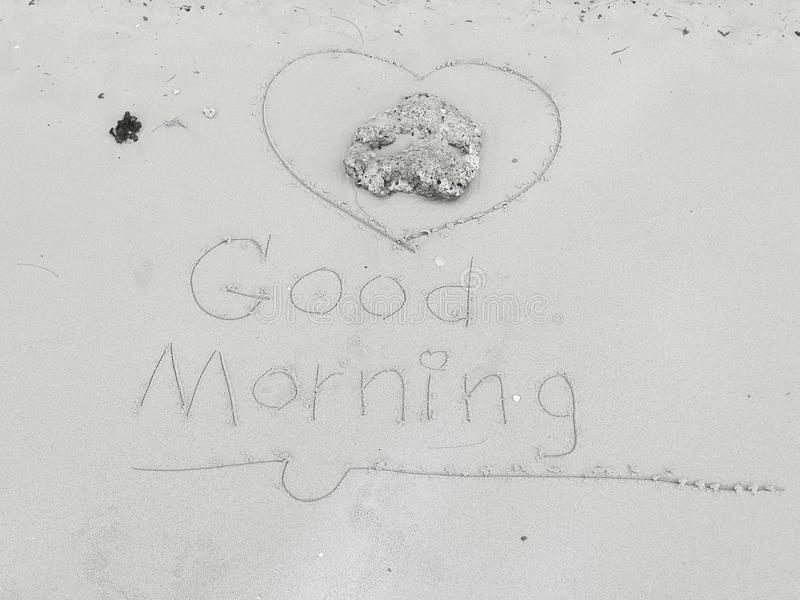 Rock and handwritten `Good morning & heart`on sand beach royalty free stock images