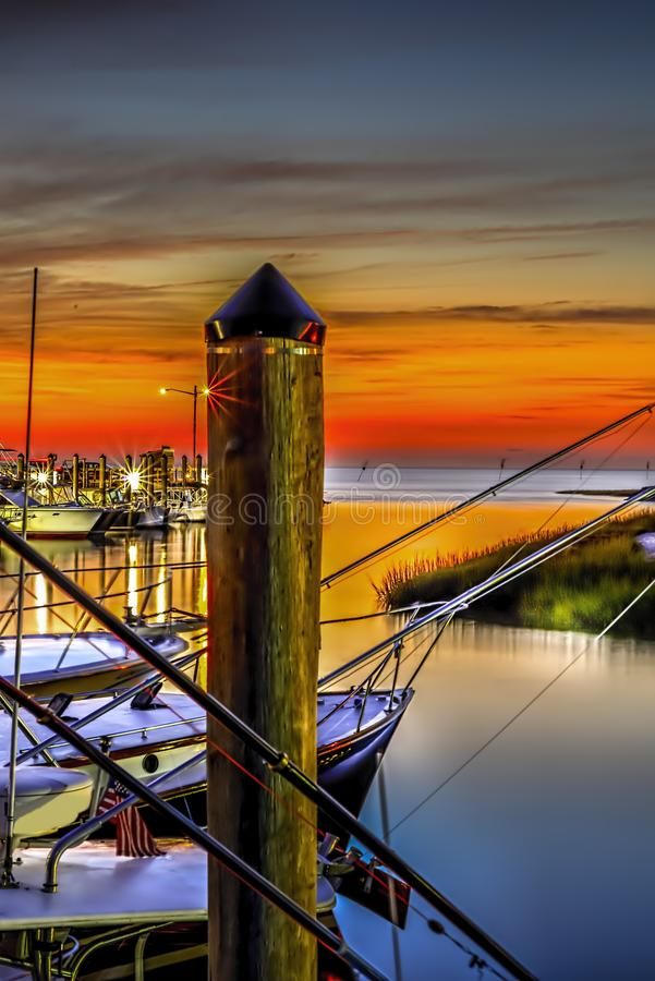 Rock Harbor with boats at dock at sunset stock photography