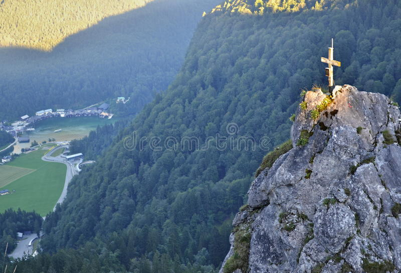 Rock with illuminated cross above a valley stock image