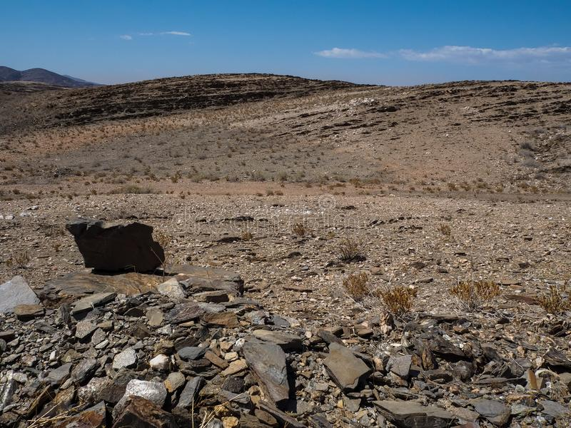 Rock mountain dried dusty landscape ground of Namib desert with splitting shale pieces, other stone, desert plant and blue sky. Namibia stock photography
