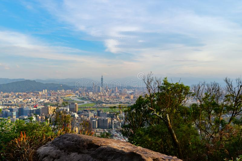 Rock on mountain hill in Taipei downtown with copy space, Taiwan in adventure concept during travel trip, vacation, or holidays. Skyscraper and high-rise stock images