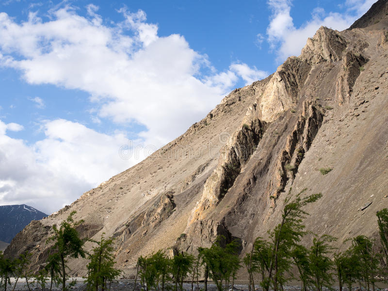 Rock mountain ridge and trees with blue sky with cloud as background. Annapurna Conservation Area, Nepal stock photo