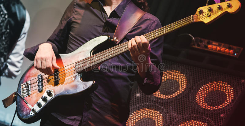 Rock music, bass guitar player on a stage. Rock music concert, bass guitar player on a stage, selective focus royalty free stock image