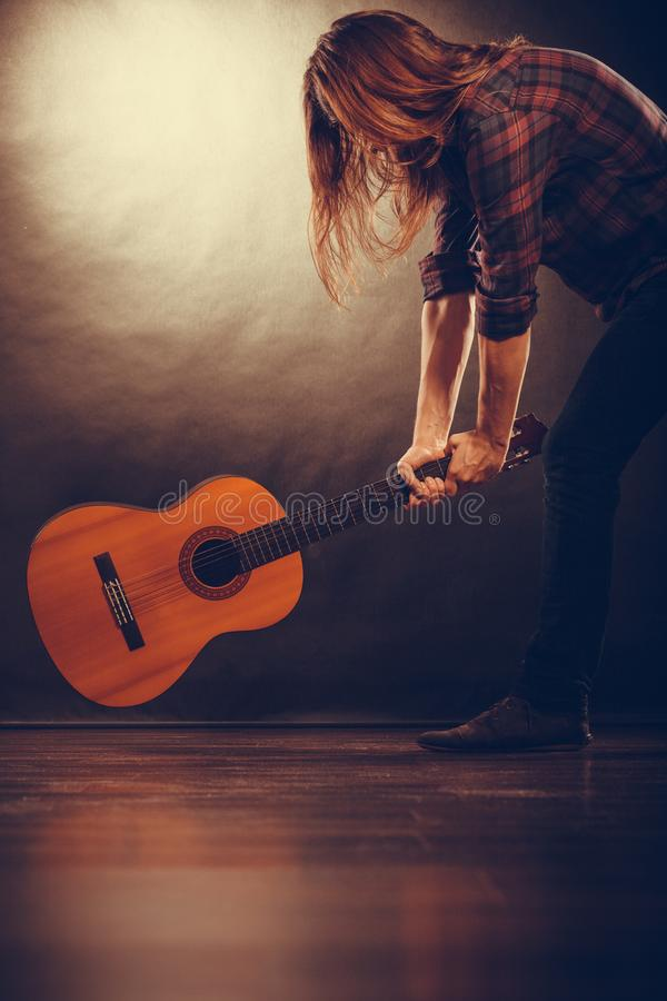 Rock musician destroys his guitar. Rock music energy people feelings concept. Mad rock guitarist destroys his guitar royalty free stock image