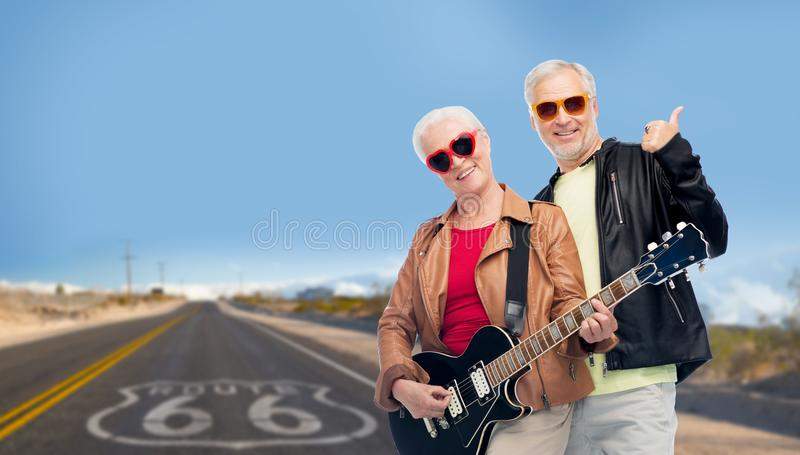 Senior couple with guitar over route 66. Rock music, old age and travel concept - happy senior couple with electric guitar over us route 66 background showing stock images