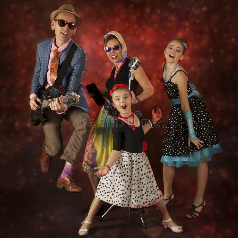 Rock musician family having fun. Rock musician family have fun playing music and singing on a black background with glowing lights stock images