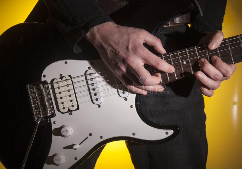 Rock musician playing electric guitar. Music note notes strings hand composers artist tapping stock photography