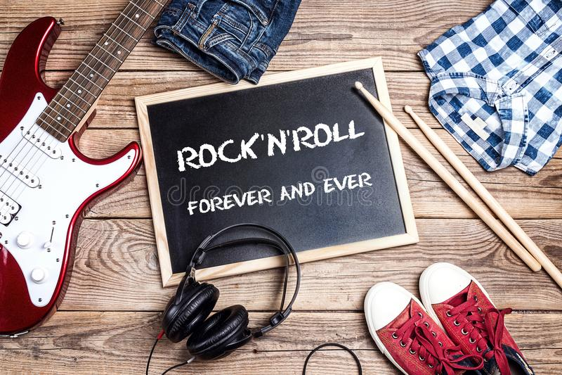 Rock`n`Roll background with blackboard, music equipment, clothes royalty free stock photography