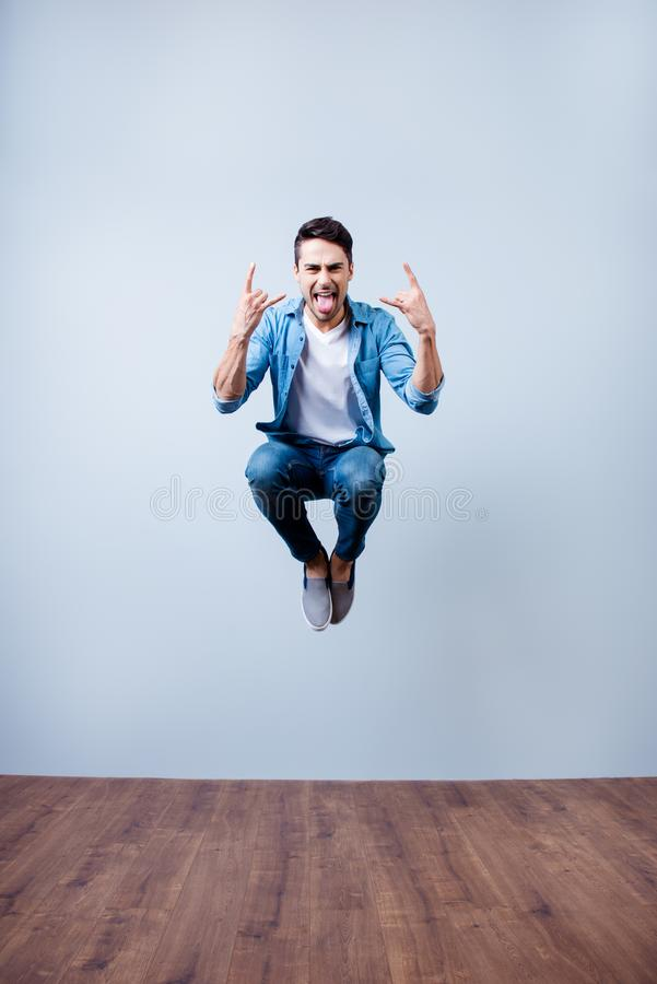 Rock n roll! Go crazy! Happy young brunete guy is jumping and fooling around. He is in casual jeans wear and tongue out stock image