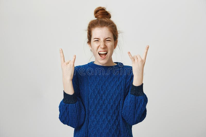 Rock n roll lives in us. Portrait of excited and thrilled young european redhead girl screaming from positive emotions stock photos