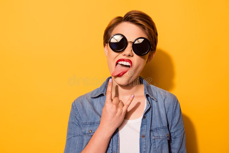 Rock n roll! Portrait of a playful young stylish girl with tongue out. She is in a jeans shirt and has a bright red royalty free stock images