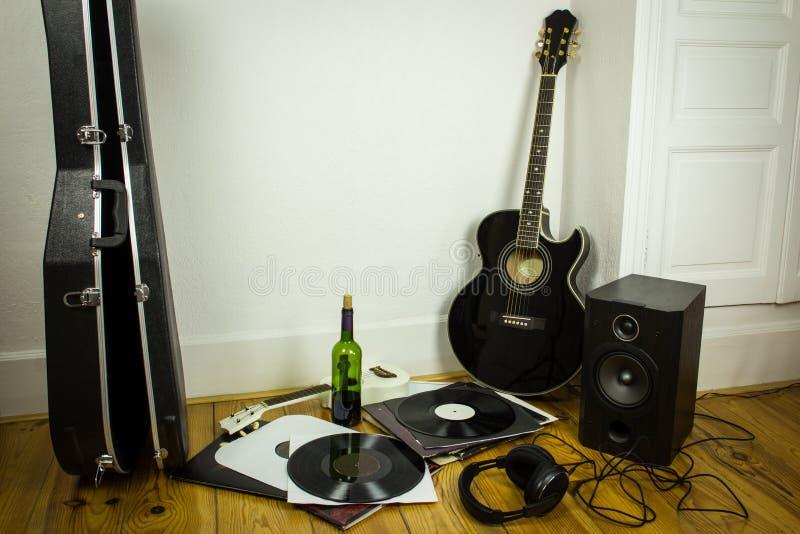 Rock'n'roll setup with ukulele, acoustic guitar, speaker, vinyl. Records, bottle of wine and headphones on wooden floor stock photos