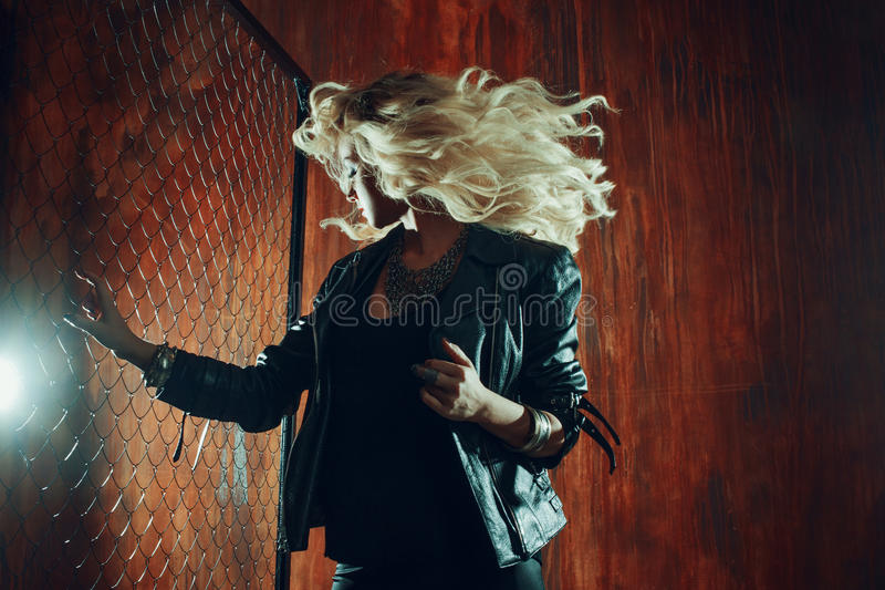 Rock ` n ` Rollenmädchen, junge Schönheit tanzt in dunkle Gasse, gegen die Zaunmasche lizenzfreie stockbilder