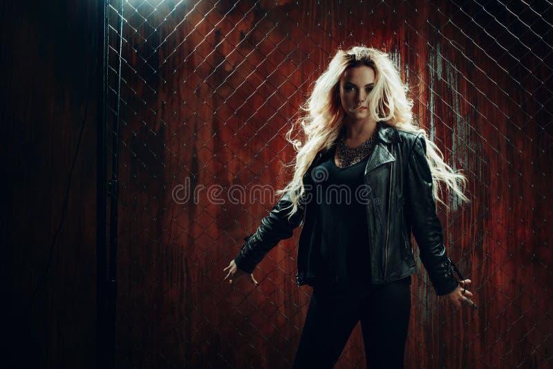 Rock ` n ` Rollenmädchen, junge Schönheit tanzt in dunkle Gasse, gegen die Zaunmasche lizenzfreie stockfotos