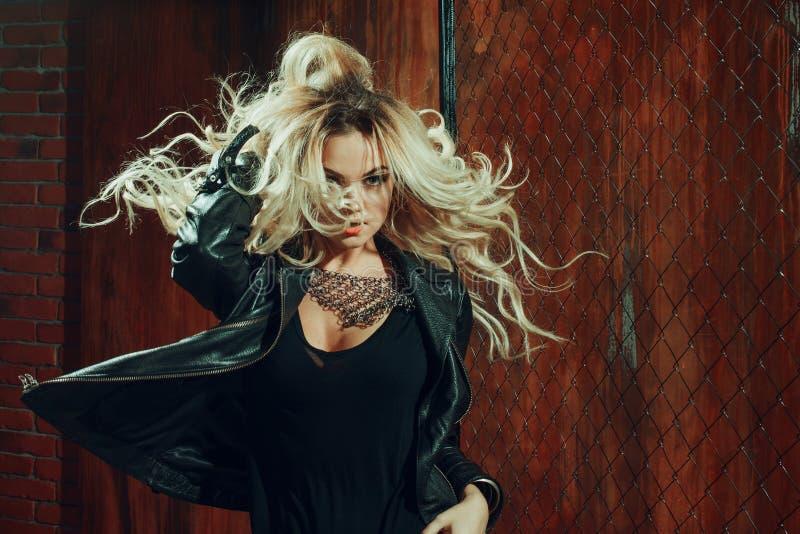 Rock ` n ` Rollenmädchen, junge Schönheit tanzt in dunkle Gasse, gegen die Zaunmasche lizenzfreies stockbild
