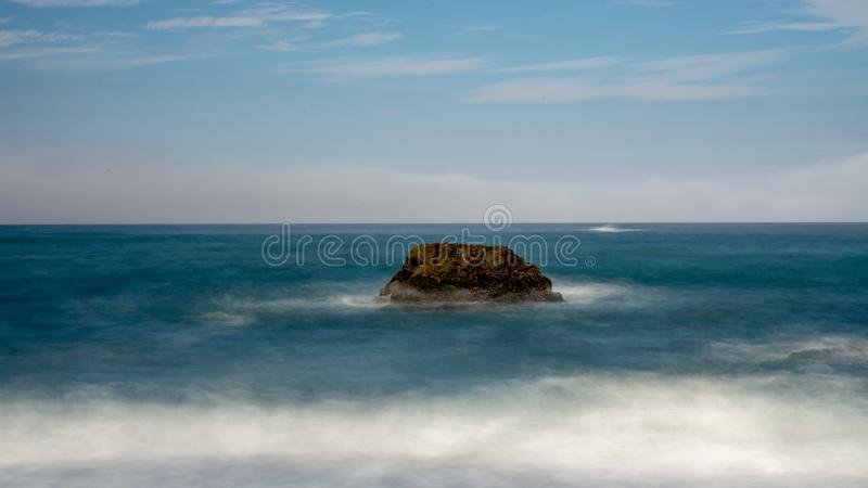 A rock in the ocean at Bodega Bay. A rock in the ocean by Bodega Bay long exposure featuring blue water and sky - ample copy space abstract composition stock images