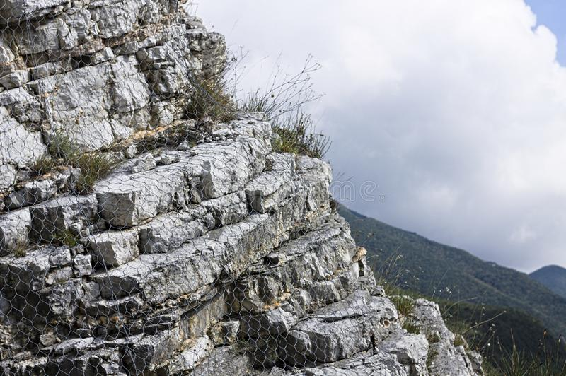 Rock outcrop with a wire mesh stock image