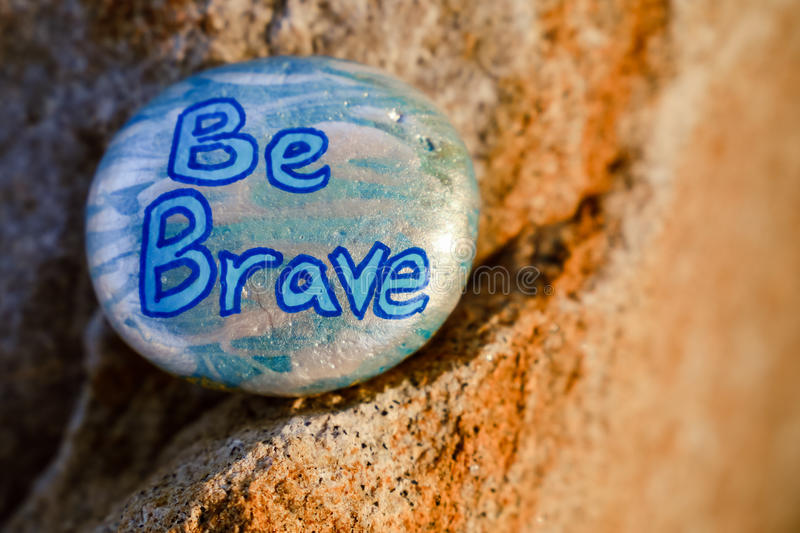 A rock painted silver and light blue stating Be Brave royalty free stock image