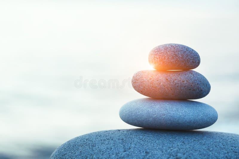Rock pebble pyramid, zen stones on sea beach. At morning sunrise, meditation, spa, harmony, calm and balance concept, copy space royalty free stock photo