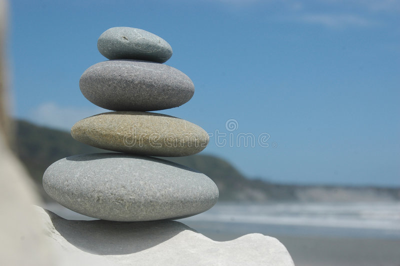 Rock pile. Smooth rocks stacked up with beach scene in background royalty free stock photo