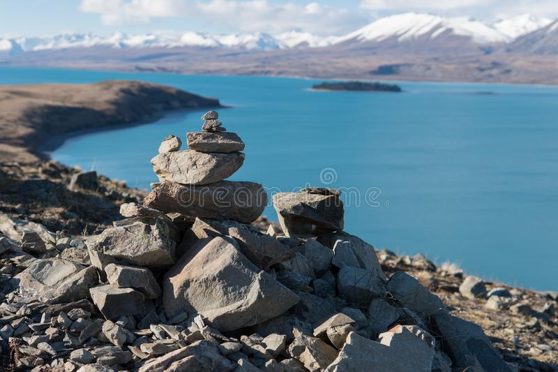 Rock pile on Mountain at Lake Tekapo. In New Zealand with mountains and lake in the background in winter stock photo