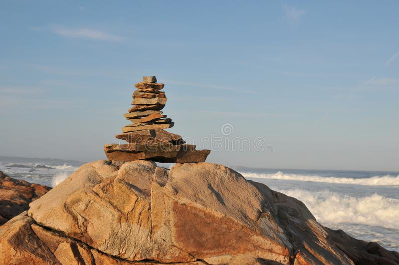 Rock Pile. At Bass Rocks in Gloucester, Massachusetts, with surf from Hurricane Humberto in the background royalty free stock image
