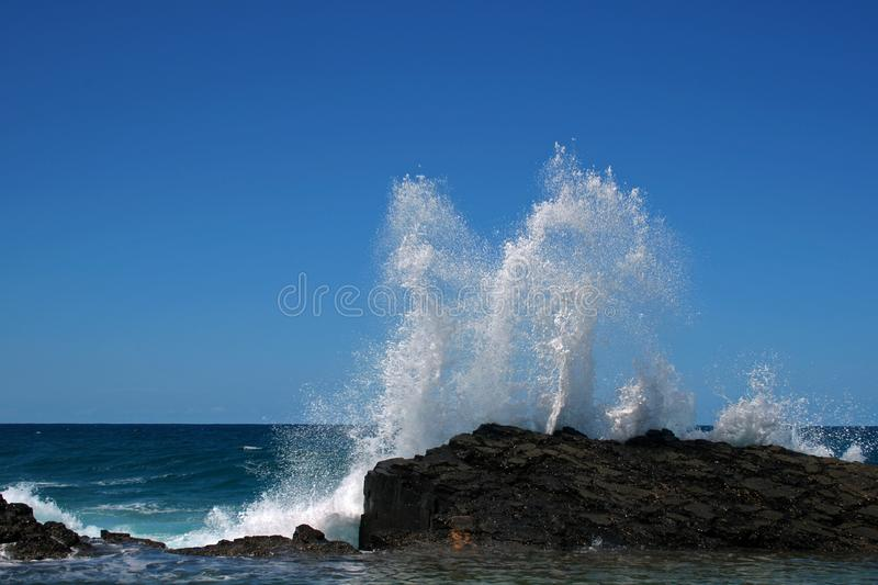ROCK POOL WITH SURF SPLASHING HIGH. Image of sea with white surf crashing over rocks into a tidal pool royalty free stock image