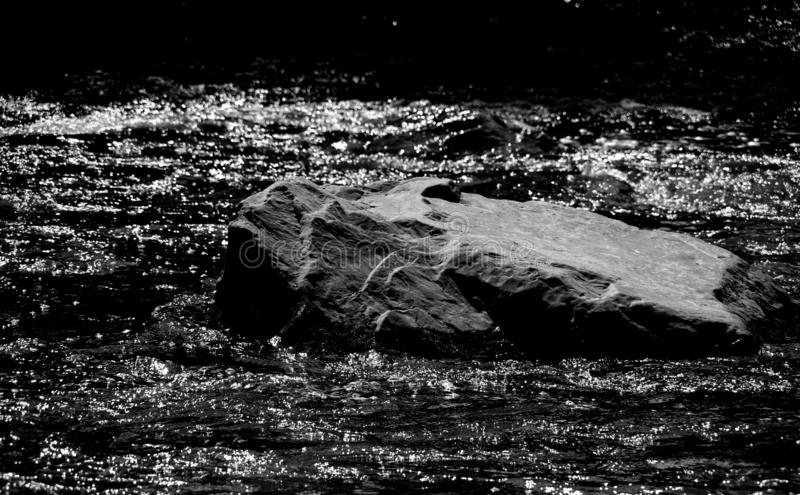 Big boulder in glistening water in black and white stock photography