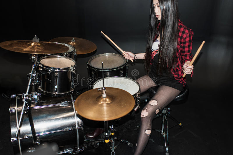 Rock and roll girl playing hard rock music with drums set stock image