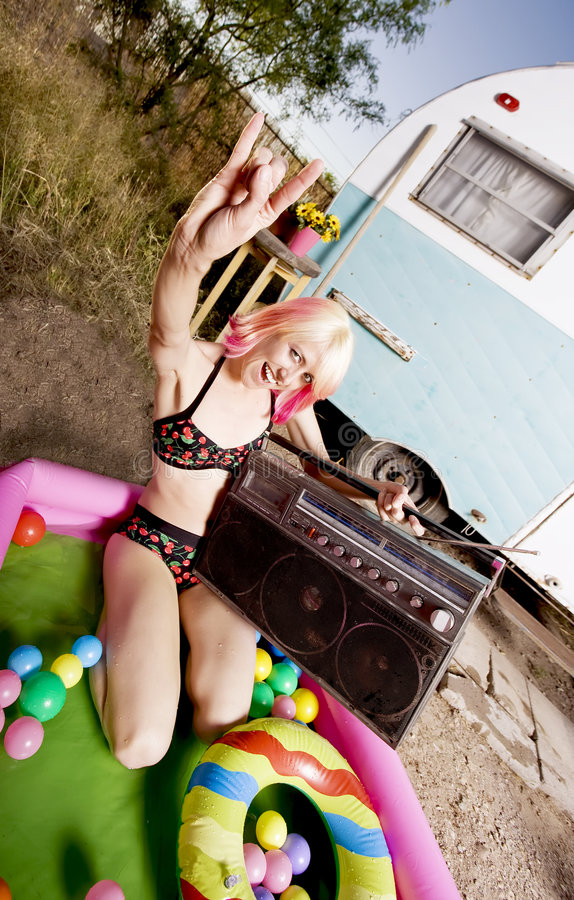 Rock and Roll Woman in a Play Pool. Woman with a boom box in an inflatable play pool royalty free stock photo