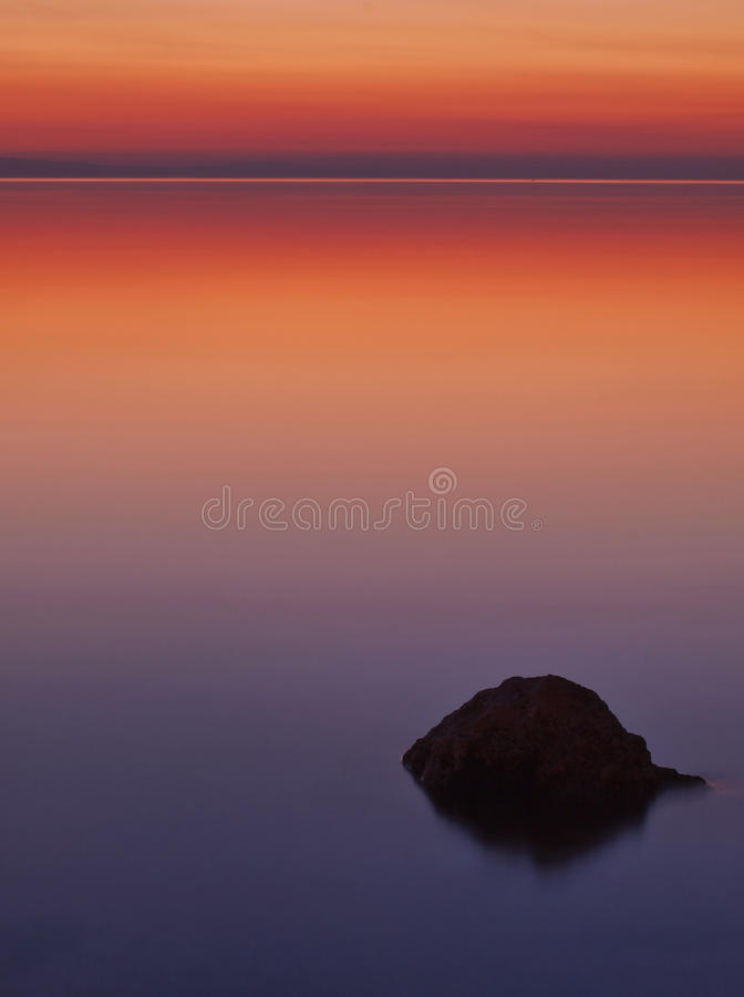 A rock in the sea at sunset