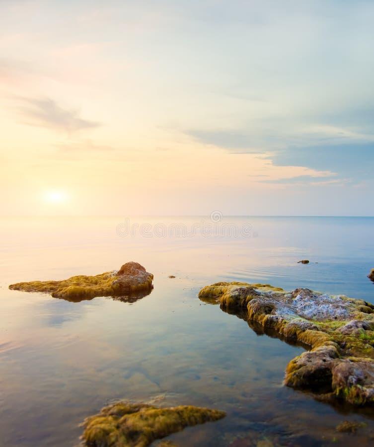 Rock in sea on sunset. stock photos