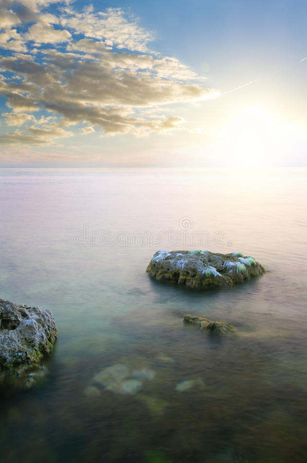 Rock in sea on sunset. royalty free stock photos