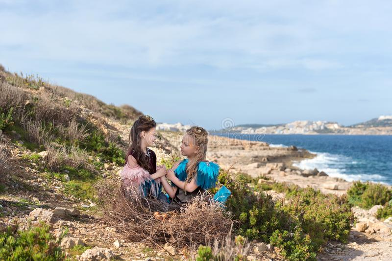 On a rock on the seashore in a huge nest with eggs sit two girls dressed in fairy birds hold hands and look eyes in the eyes royalty free stock image