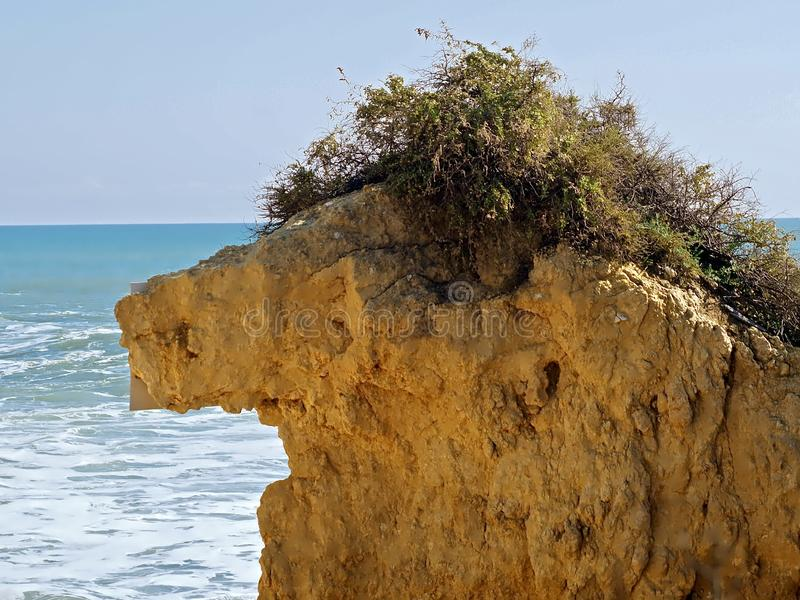 Rock in the shape of the famous figure Alf. In front of blue ocean royalty free stock images