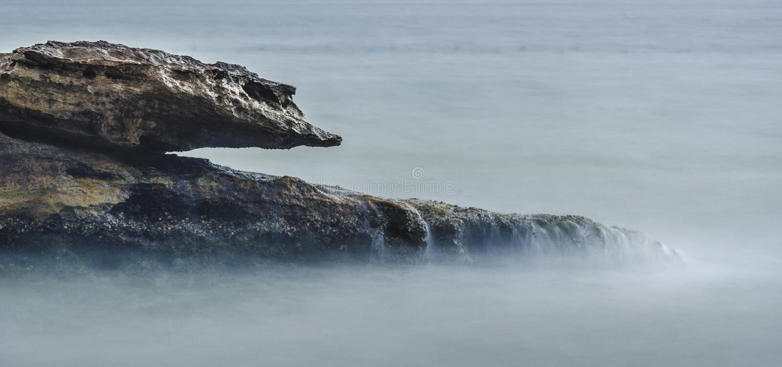 Download Shaped rock in the ocean stock photo. Image of tranquil - 30139354
