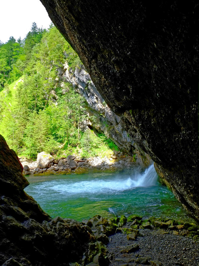 Rock shelter at waterfall basin in alpine geopark. The basin of the Buchenegger waterfalls - a scenic attraction in the nature park Nagelfluhkette in Allgau stock photos