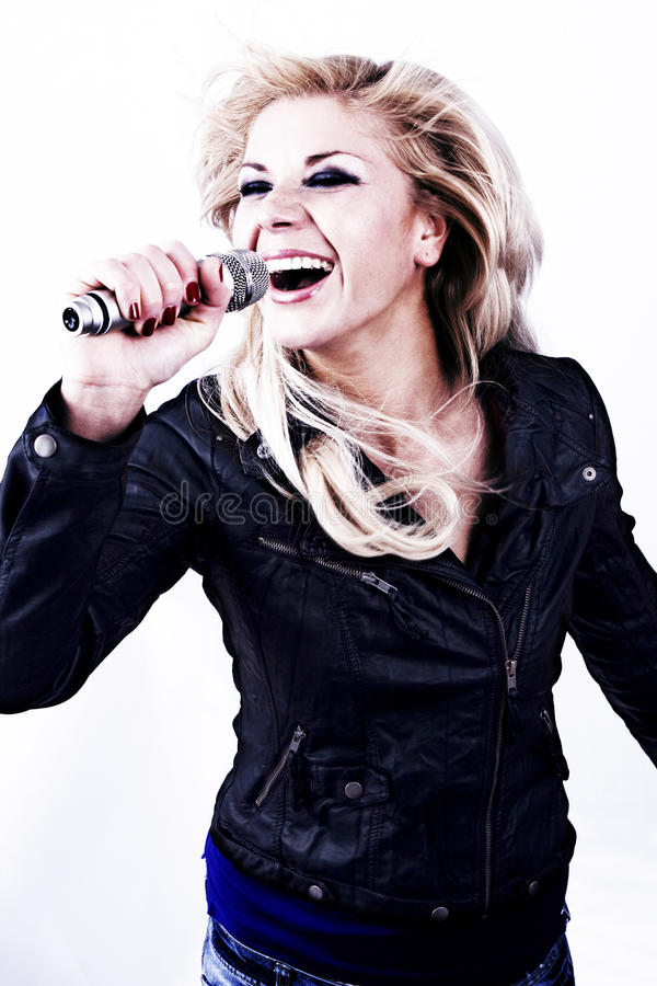 Rock singer. Young girl singing into microphone. Rock Singer. Pretty girl singing into microphone. Young female singer with blond hair singing a song. Woman stock photography