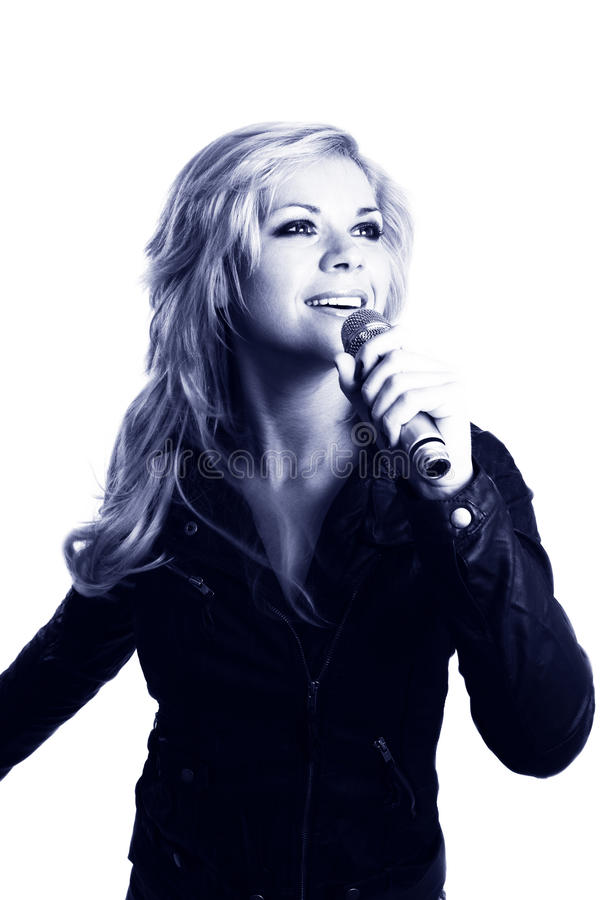 Rock singer. Young girl singing into microphone. Rock singer. Pretty girl singing into microphone. Young female singer with blond hair singing a song. Woman stock photo